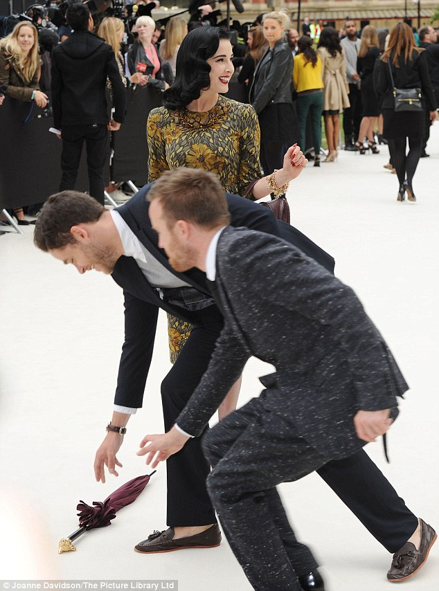 Help at hand: But Breaking Bad actor Aaron Paul, left and a helpful PR man right, came to her rescue as they handed back her accessory from the floor