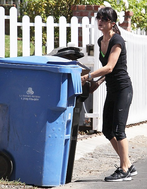 What a chore: Selma also worked up a sweat when she pushed some heavy bins out onto the street in front of her home