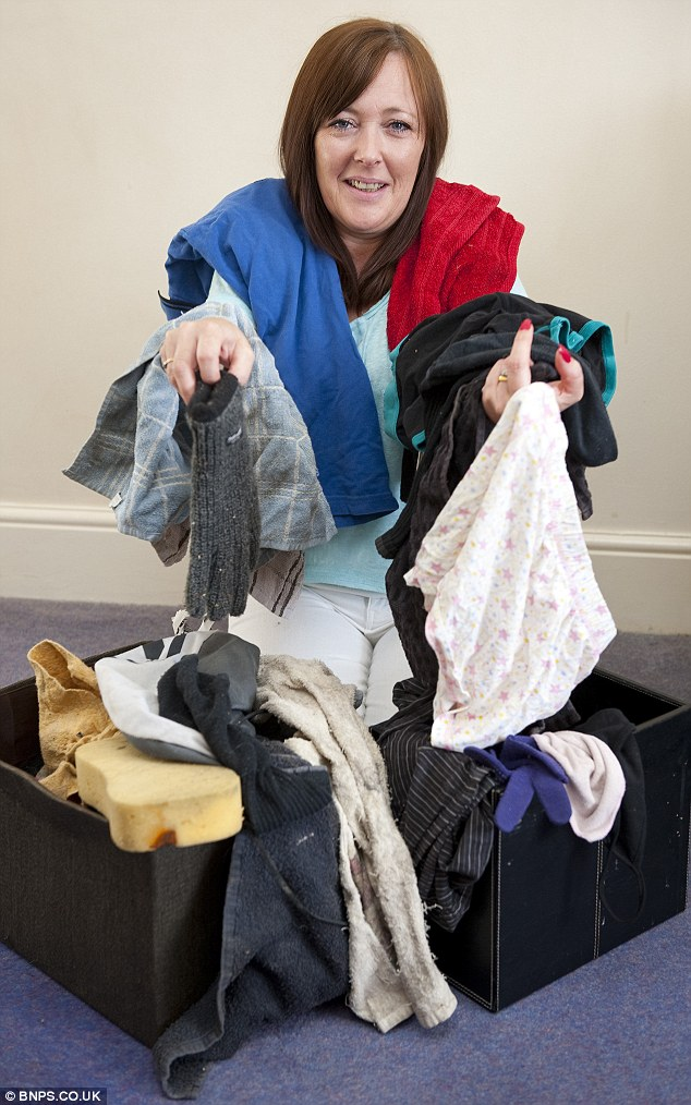 Embarrassed Mrs Newman shows off the two boxes full of clothing and toys that two-year-old Denis has pinched over the last 18 months