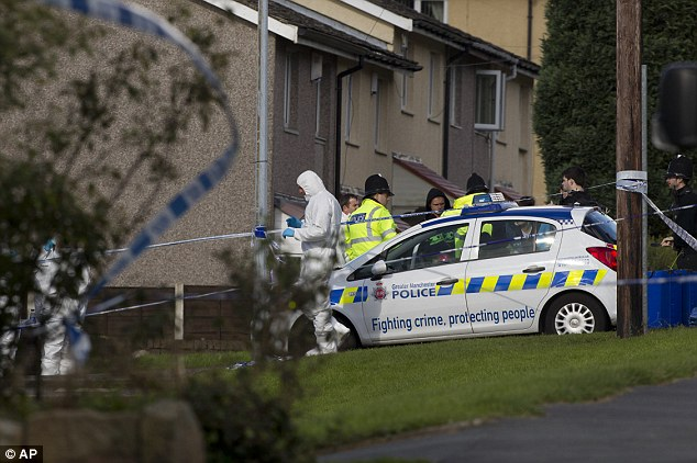 Investigation: Police forensics staff work near the scene in Greater Manchester where two unarmed female police officers were killed in a gun and grenade attack, which led to the arrest of a wanted man