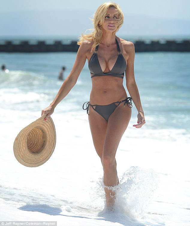 Beach babe: Camille Grammer put her ample cleavage on display in a stone-coloured bikini as she enjoyed a day at the beach in LA
