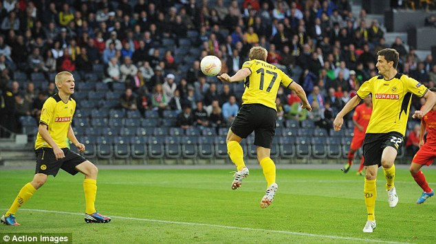Oh dear: Juhani Ojala (left) puts the ball into the back of his own net