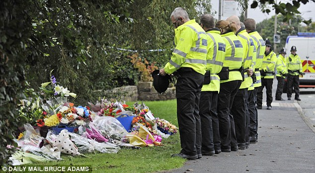 Respectful: Police officers stand in a line to read floral tributes at the scene where the shootings happened