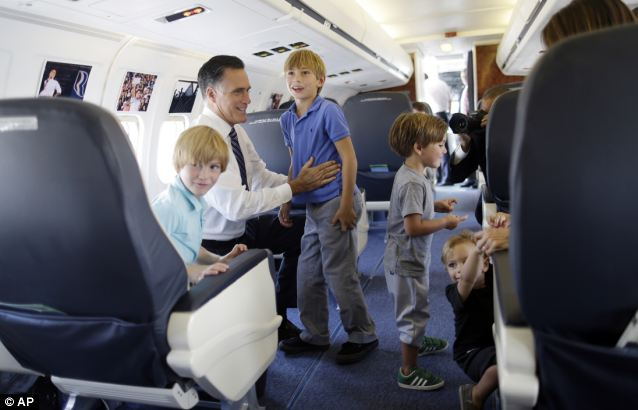 Turbulent times: Mitt Romney with his grandchildren on his campaign jet on Tuesday