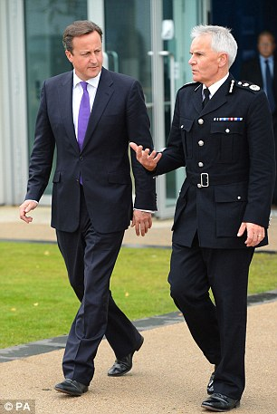Prime Minister David Cameron (left) speaks with Chief Constable of Greater Manchester Police Peter Fahy (right) as he leaves Greater Manchester police headquarters following his visit today