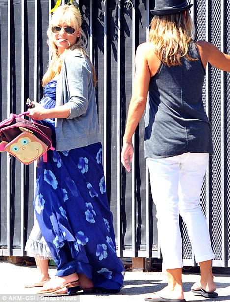 Parenting duties: She carried her daughter, Charlotte's monkey backpack in one hand and held her girl's hand with the other in Santa Monica, California