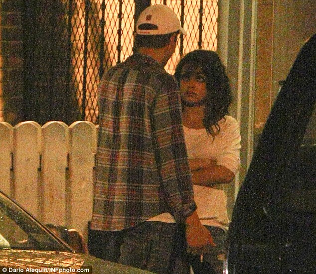Can we go home? Kunis looked tired as she waited for her man to finish smoking