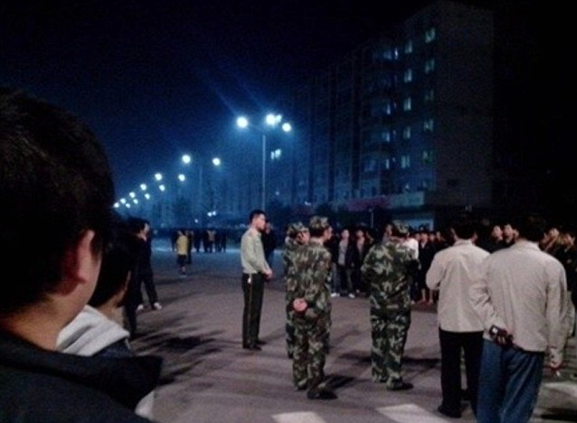 Members of the military appear opposite the protesters on the streets outside the factor