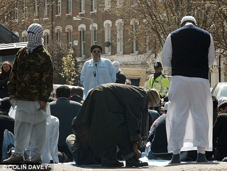 Worshippers: Hamza (pictured centre, wearing blue) earned global notoriety for his vile sermons outside the Finsbury Park Mosque