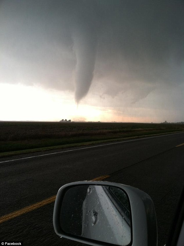 Strength: A funnel cloud is captured from a highway, one of several spotted whose strong winds in all would tear off roofs and turn over at least two semis