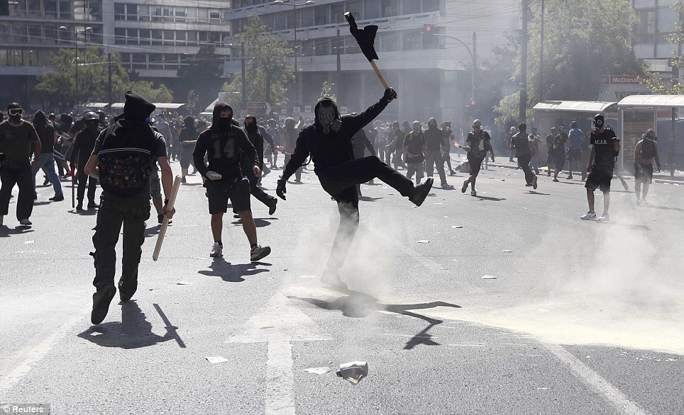 A demonstrator kicked a tear gas cannister to riot police near Syntagma square during a 24-hour labour strike