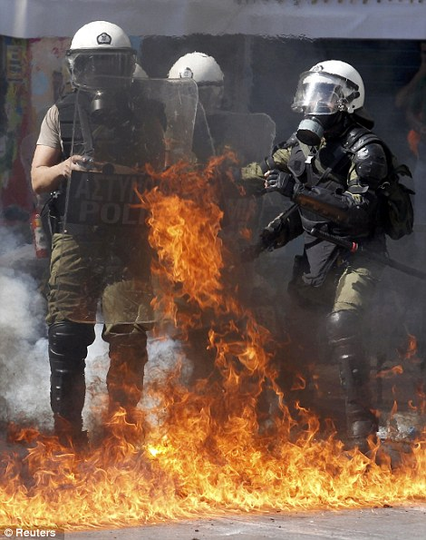 A riot police officer prepares to throw a tear gas cannister at protesters during clashes near Syntagma square during a 24-hour labour strike