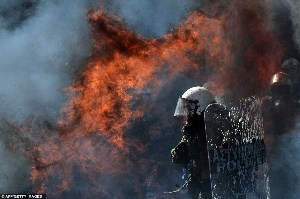 Fire ball: A Molotov cocktail explodes near riot police, thrown by hooded youths after the large demonstration turned violent