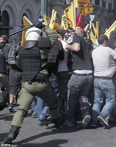 A baton-wielding riot policeman hits out at retreating protesters in Athens