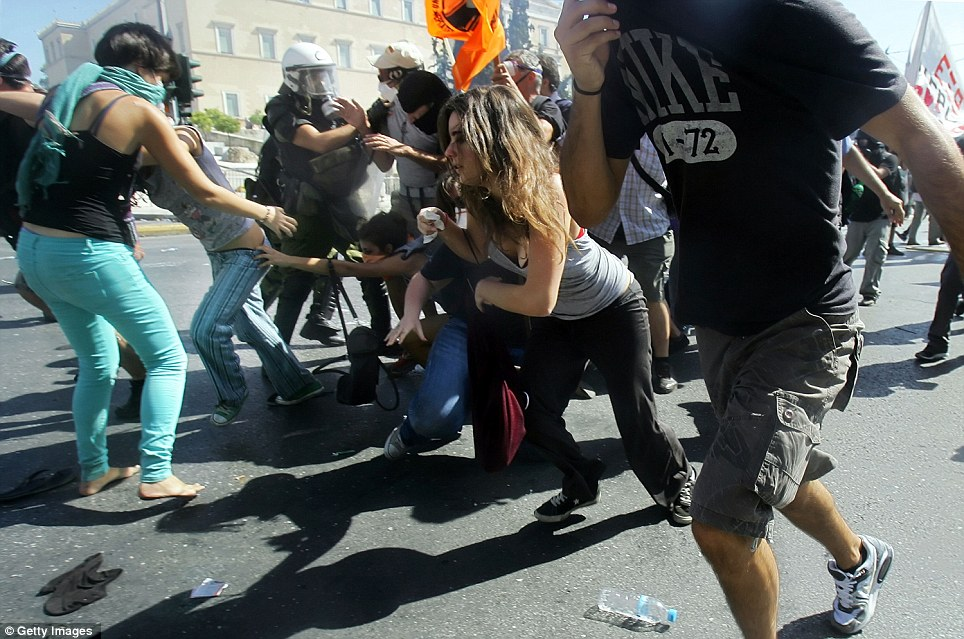 Demonstrators run as they clash with riot officers. About 3,000 police - twice the number usually deployed - stood guard in the centre of Athens