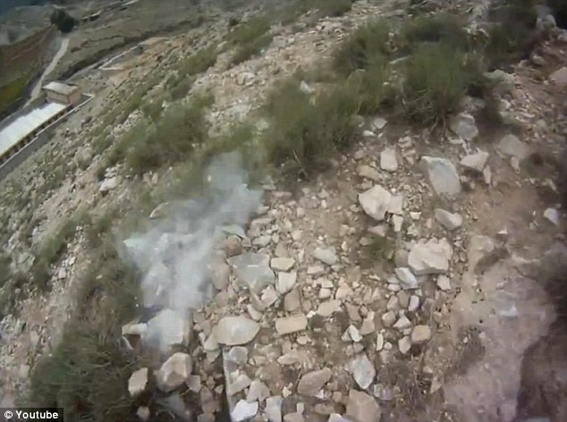 Too close for comfort: Dust kicked up by a bullet can be seen on the video, right near the soldier's feet as he descends the mountain