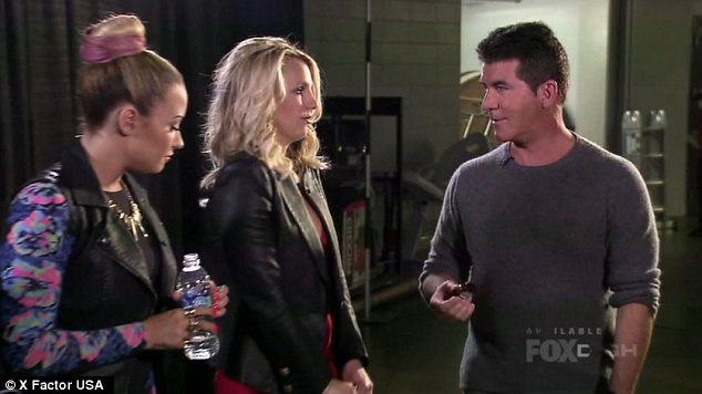Telling off: Britney Spears appears to be being scolded by her boss Simon Cowell, while Demi looks on