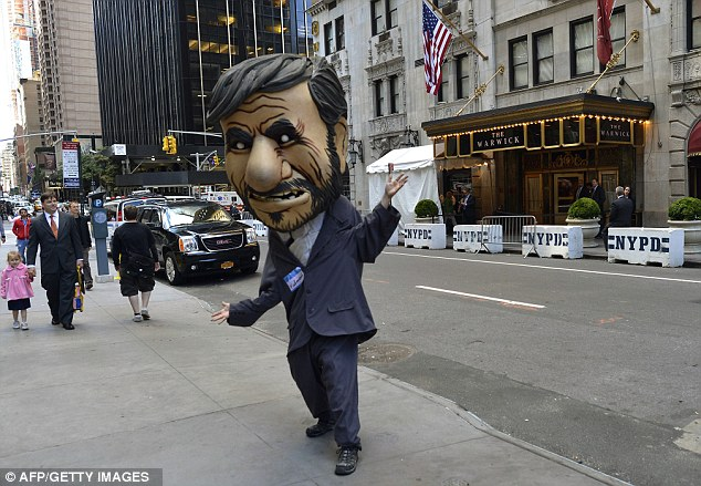 Opposition: A protestor in a President Ahmadinejad head demonstrates outside the Warwick Hotel