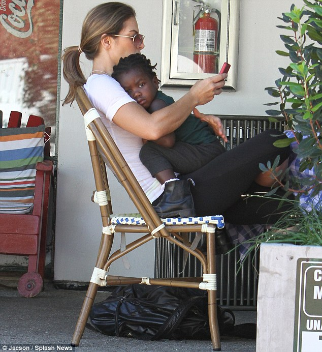 Cuddling up: Jillian Michaels gave adopted daughter Lukensia a hug as she sat at a Malibu cafe on Thursday