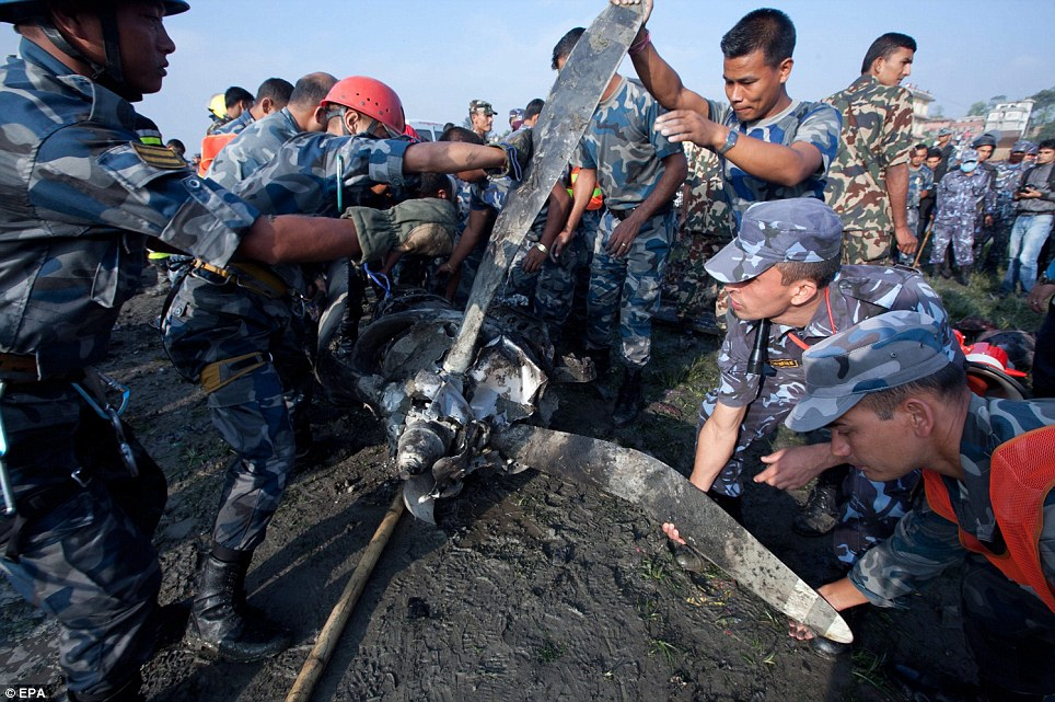 Picking through the pieces: A recovery team clears away one of the propellers as investigators try to establish what caused the crash which killed all 19 people on board