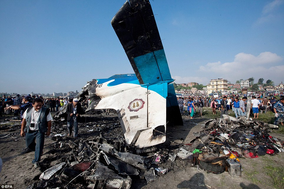 Decimated: Rescuers inspect the wreckage of a plane which crashed on the edge of the Nepalese capital Kathmandu minutes after take-off, killing seven British trekkers