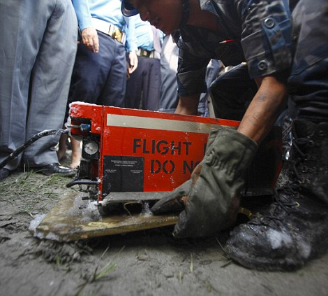 A Nepalese police officer carries a black box after it was recovered from the crash site