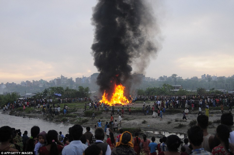 Doomed: Mobile phone video shot by locals showed the front section of the plane was on fire when it first hit the ground