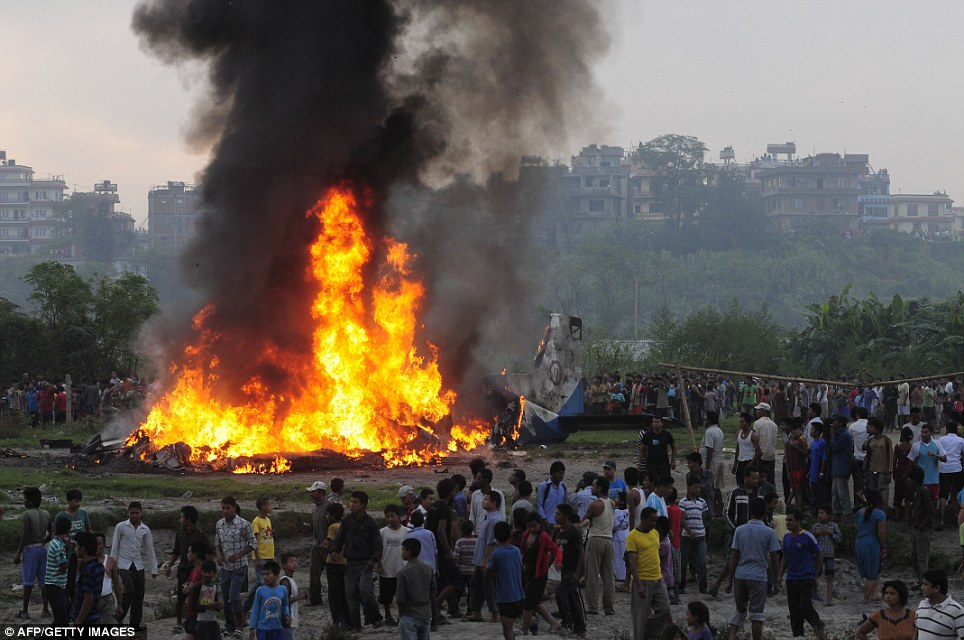 No survivors: Onlookers watch on helplessly around the blazing plane which crashed on the edge of the Nepalese capital, killing 19 people including seven Britons