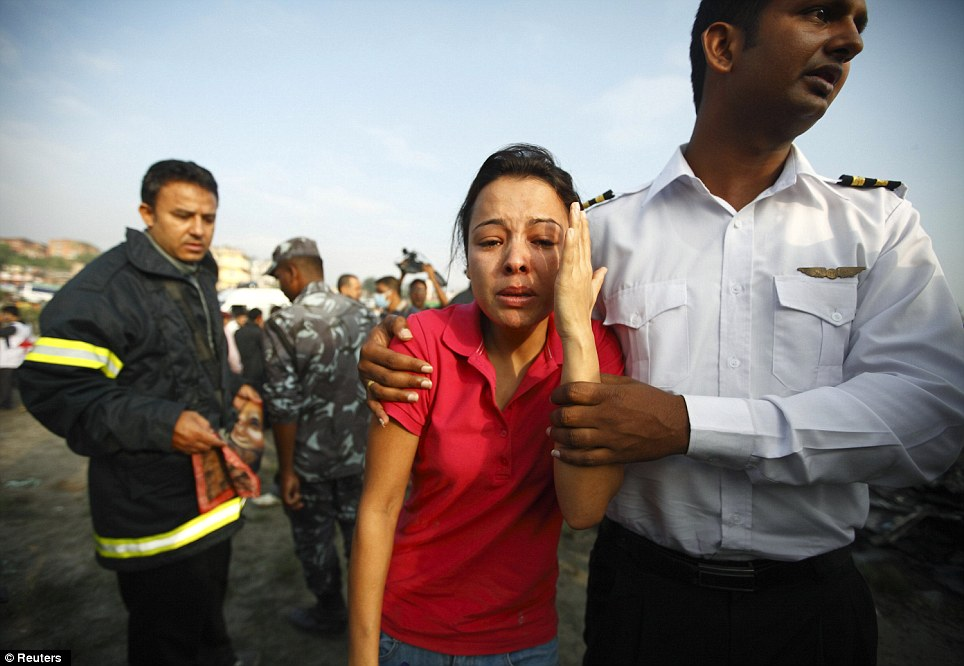 Distressing: A woman is comforted as she cries at the crash site. It is not known if she is a relative of anyone on board