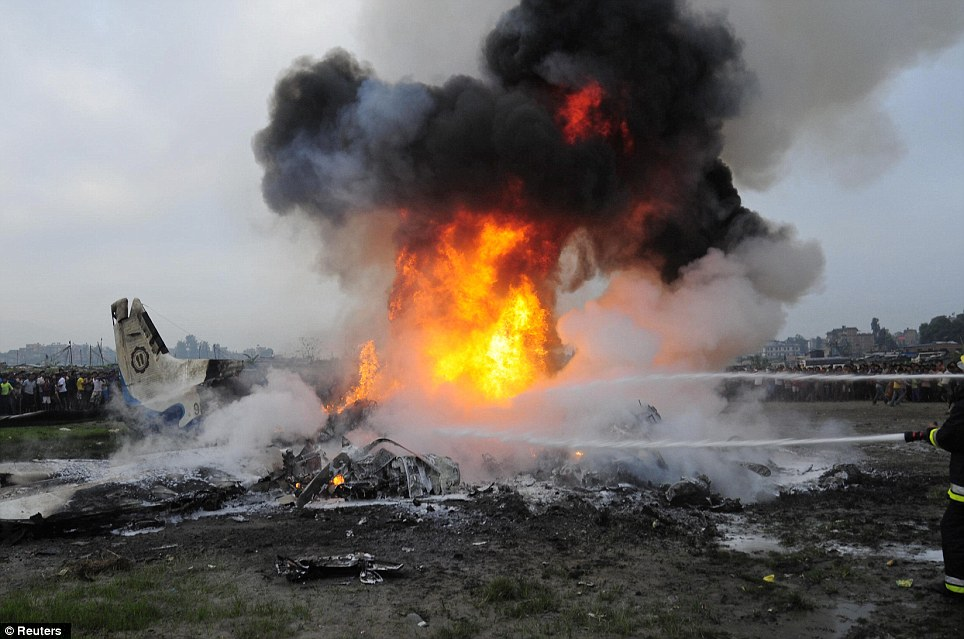 Fireball: Firefighters battle to douse the burning wreckage of a plane after it came down in a field just minutes after takning off from Kathmandu Airport