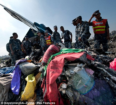 Nepalese police officers stand around the wreckage of the Sita Air Dornier Aircraft