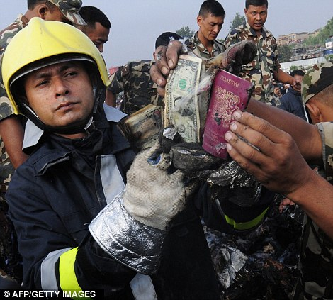 Nepalese fireman and rescue workers show a passport and money
