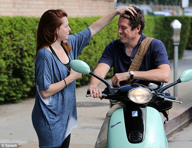Affectionate: Alyson was seen playing with her husband's hair as he sat on his mint green moped