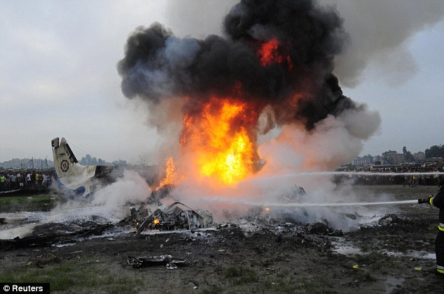 Fireball: Firefighters battle to douse the burning wreckage of a plane which crashed on the edge of the Nepalese capital, killing 19 people including seven Britons