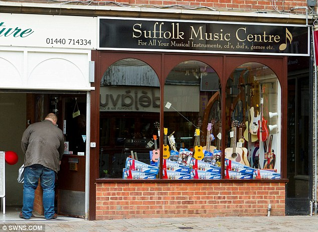Business as usual: Mr Bayford, opens his store in Haverhill, Suffolk, before getting down to work