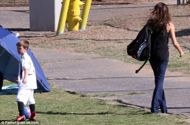 Little star: Cruz sported a number 23 jersey and red boots, while Victoria carried his backpack