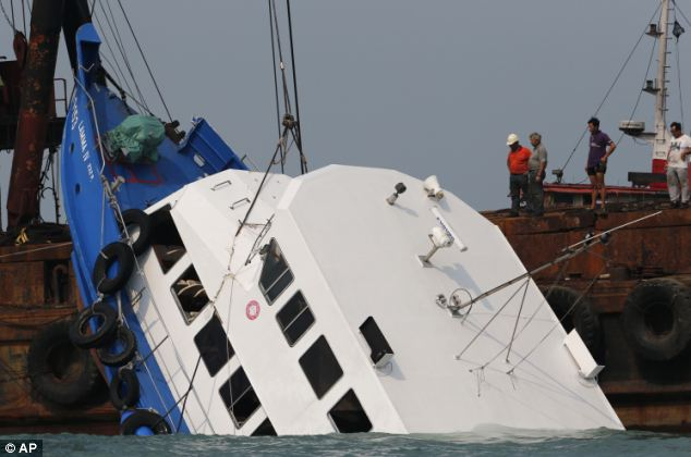 Tragedy: Rescuers check on the half submerged HongKong Electric boat Lamma IV after the shocking crash last night