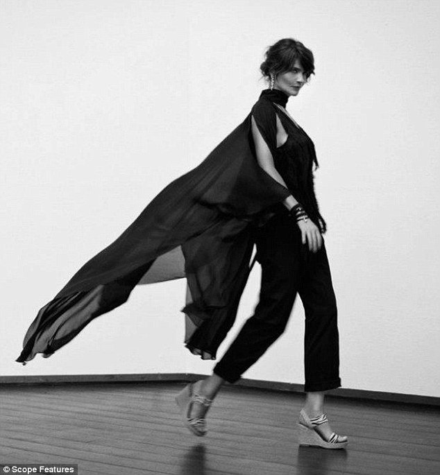 Helena smoulders in black and white shots in a flowing black cape and wedges