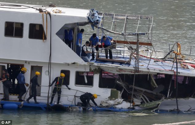 A group of firemen and police officers investigate on a salvaged boat which sank after colliding with a ferry