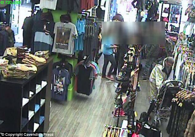 Shocking act: The thief snatches the phone from the 20-month-old's hands as she watches a Barney the Dinosaur film