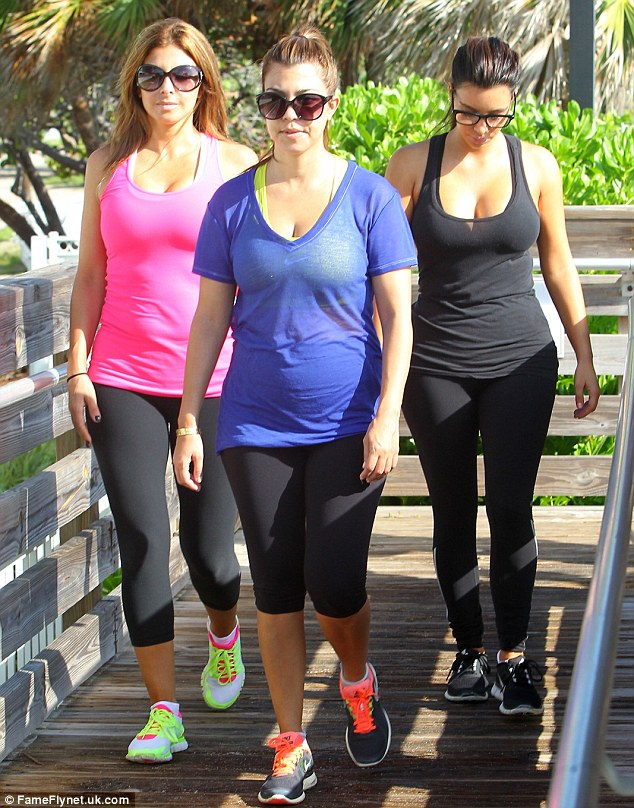 Looking good: Meanwhile, Kourtney displayed her post-pregnancy figure in some black leggings paired with a yellow sports bra worn underneath a sheer blue T-shirt