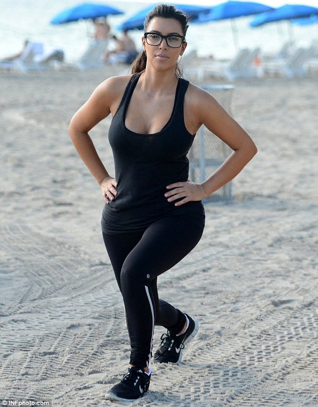 Serious about slimming down: Kim Kardashian slipped on some reading glasses as she worked out on Miami Beach on Wednesday, after revealing that she has put on weight