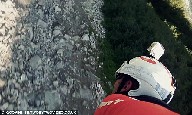 Close call: A still from the video shows just how close to the ground the wingsuit champ comes