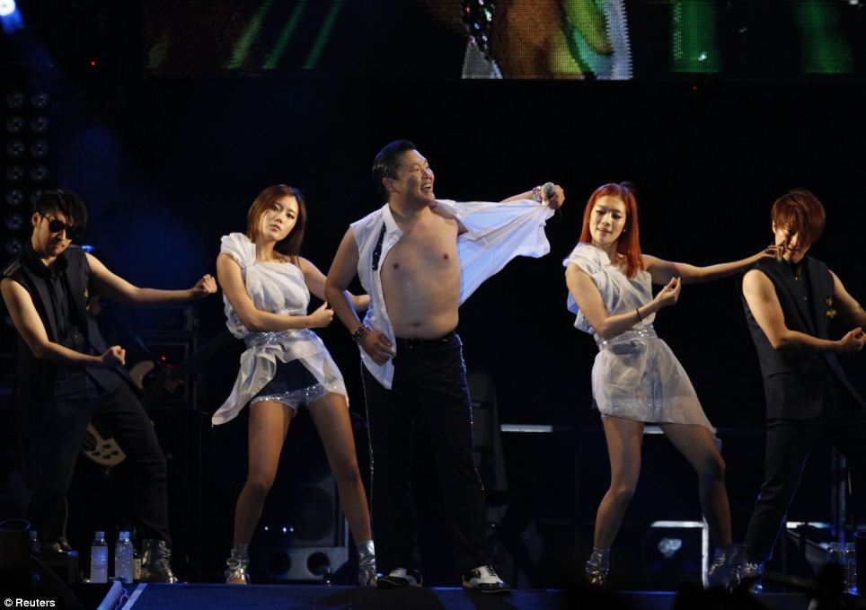 Revealing: Psy sent the crowd wild by stripping off his shirt during the glitzy performance while his backing dancers looked on