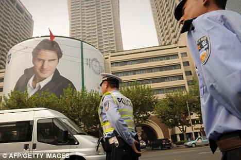 Security: A policeman is seen under a giant poster of Roger Federer in Shanghai