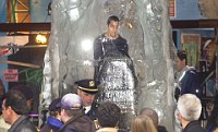 Passers-by watch illusionist David Blaine as he stands encased in ice during the last day of his endurance trial November 29,