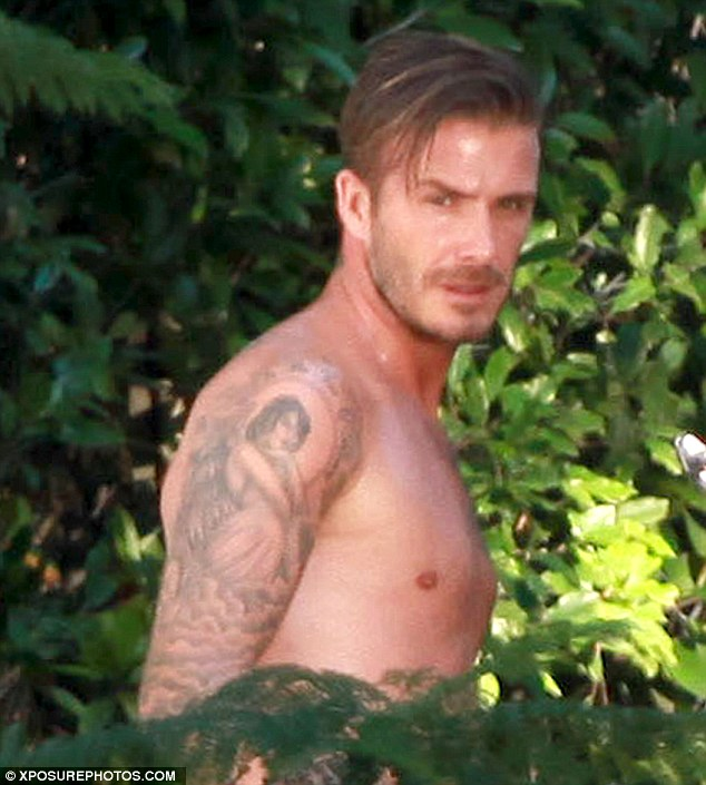Always professional: Becks even managed a sultry posed as the 'tourists' invaded his photo shoot