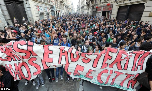 In Turin demonstrators march through the streets behind a banner urging the prime minister to stop his cut backs