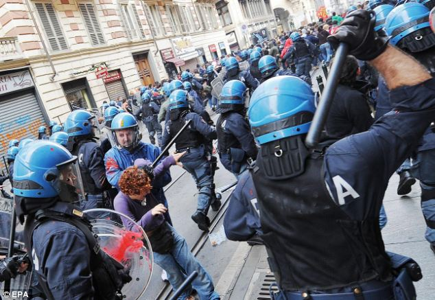 Italian riot police hit with red paint detain a protestor in the clashes