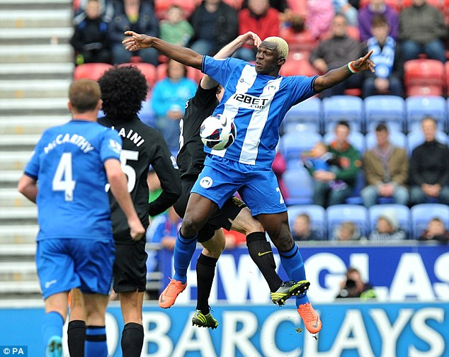 Battle: Kone appears to be pushed by his marker as he jumps for the ball